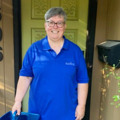 Teresa standing at front door with blue cleaning bucket